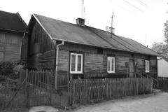 """Dom drewniany przy ul. Poetów Ulica Poetów zabudowana przez drewniane parterowe domki i niewielkie murowańce, z opuszczonymi gospodarstwami, wyłożona kamieniem polnym. Wzdłuż rosną stare drzewa, ciągną się linie elektryczne ze starymi słupami. Rażą w oczy przeprowadzone """"naprawy"""" – betonowa kostka, asfalt, trylinka. Domy na tej ulicy były budowane u schyłku XIX i na początku XX wieku. W okolicy zachowało się ich klika, nie tylko przy ul. Poetów, ale też przy pl. Światowida i ul. Tłuchowskiej."""